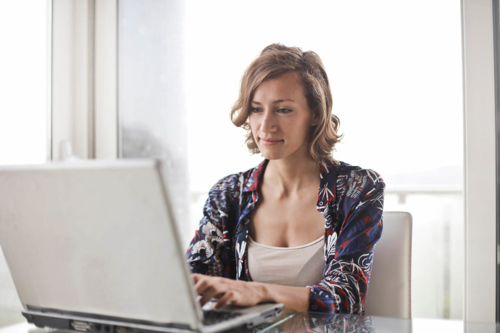 woman-in-blue-floral-top-sitting-while-using-laptop-sharemundo